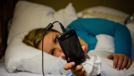 Jeune femme au lit avec son smartphone