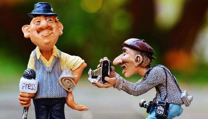 Deux figurines: un journaliste avec un micro et un photographe