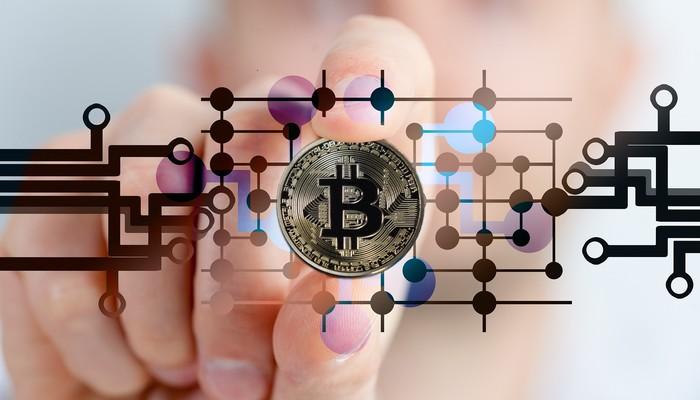 Eine Hand hällt eine Münze hoch mit eien Bitcoin zeichen drauf.