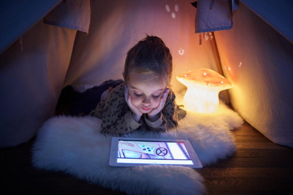 Petite fille allongée dans un tipi et qui regarde sa tablette de façon intéressante