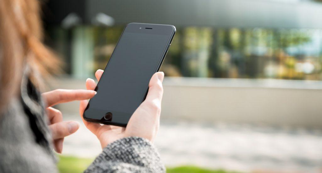 Femme tenant son Smartphone entre ses mains avec un écran noir