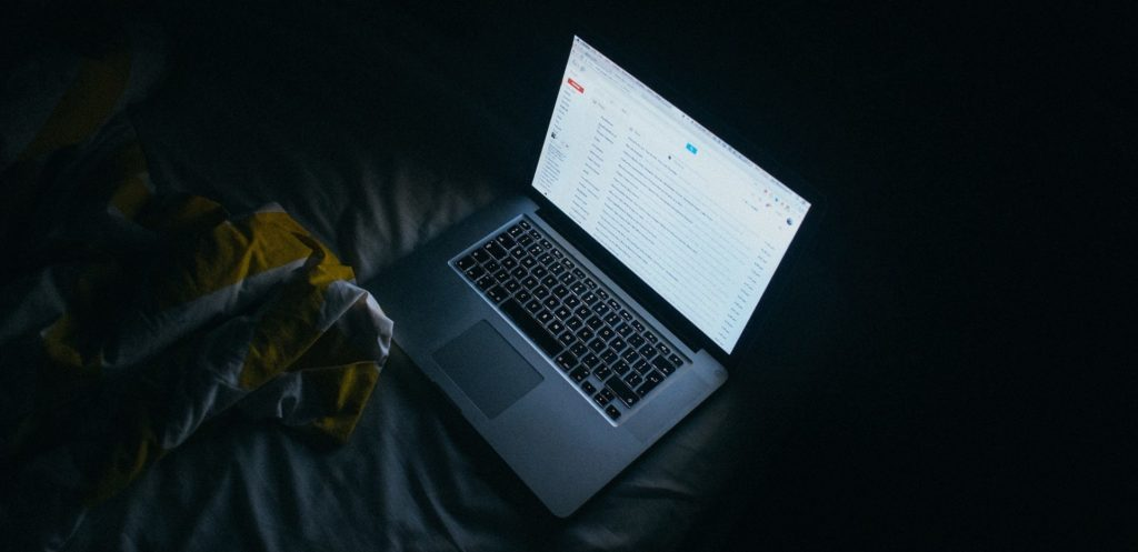 Un ordinateur portable avec l'écran allumé dans une pièce sombre