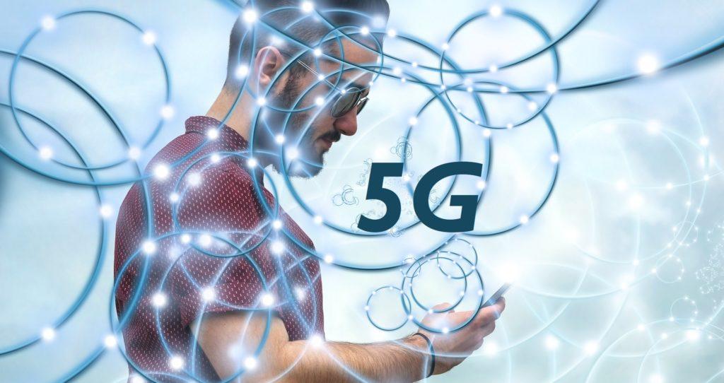 """Homme qui regarde son smartphone avec un réseau tout autour de lui et l'inscription """"5G"""""""