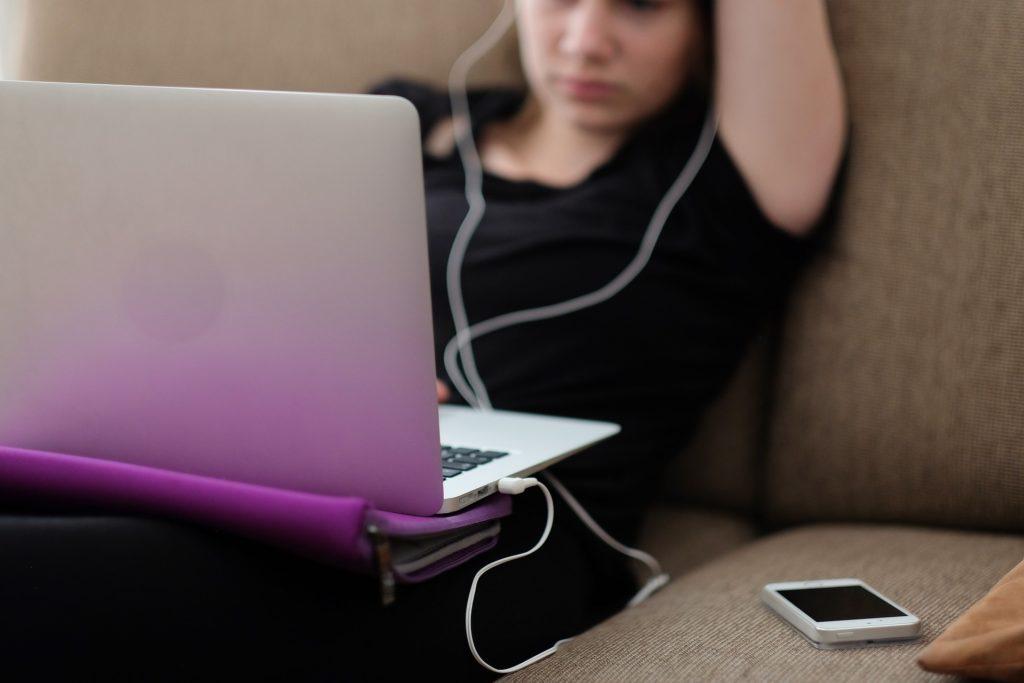 Das Laptop auf dem Schooß im Fokus, verschwommen im Hintergrund ein Mensch mit Kopfhörer und Handy