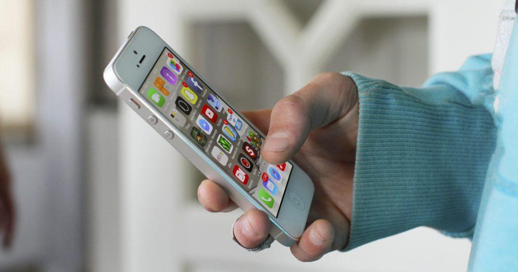 Main d'un jeune tenant un smartphone avec vue sur les applications de réseaux sociaux