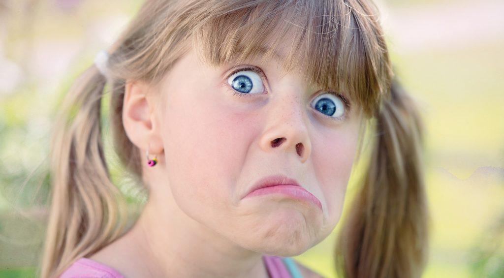 Kind was in die Kamera schaut und eine Grimasse zieht