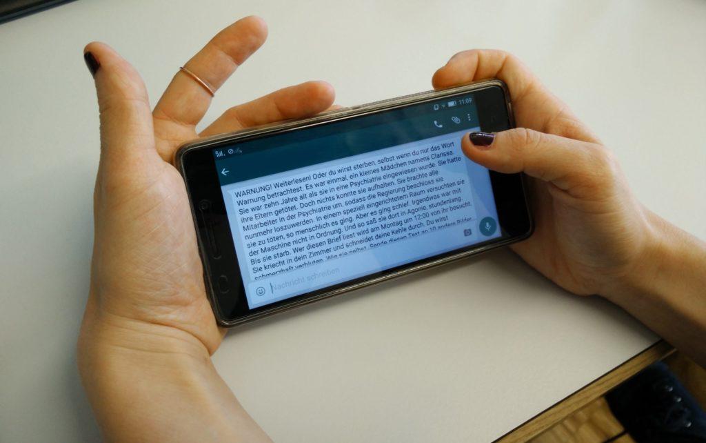 Handy in der Hand mit einer großen Warn-Meldung