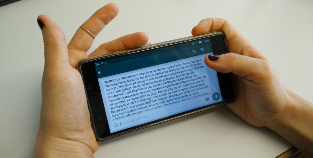Téléphone portable à la main avec un gros message d'avertissement