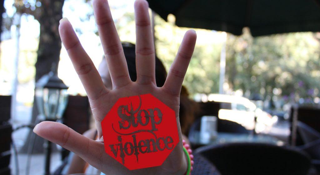 """Une personne tenant sa main vers l'appareil. Sur la main il est écrit dessus """"Stop violence"""""""