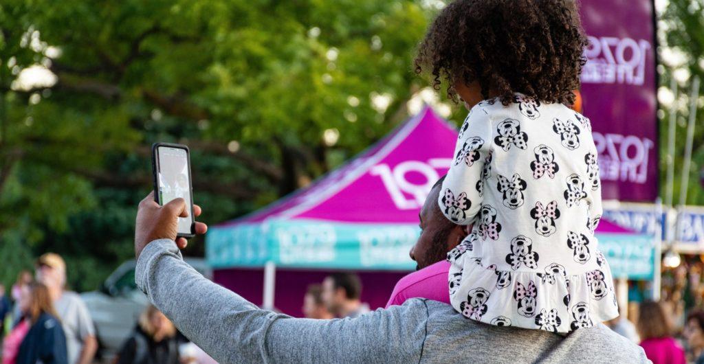 Un papa avec sa fille sur les épaules qui se prennent en selfie avec le smartphone