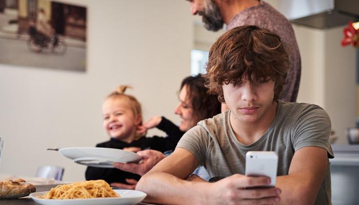 Adolescent regardant son téléphone portable pendant qu'il est à table en famille