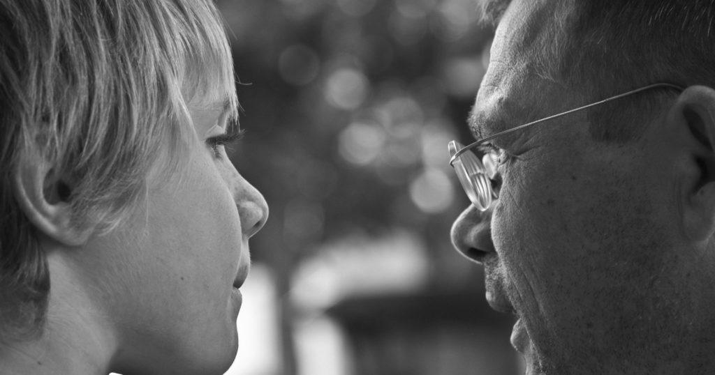 Un enfant et un adulte discute, photo en noir et blanc
