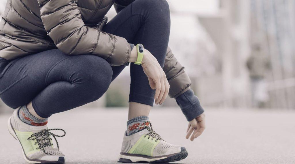 Vue coupée d'une personne accroupie en tenue de sport avec une montre connectée au poignet