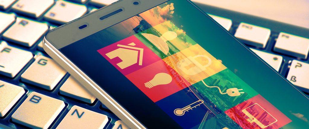 Smartphone plaziert auf einer Computertastatur. Auf dem Bildschirm erkennt man eine Smarthome-app