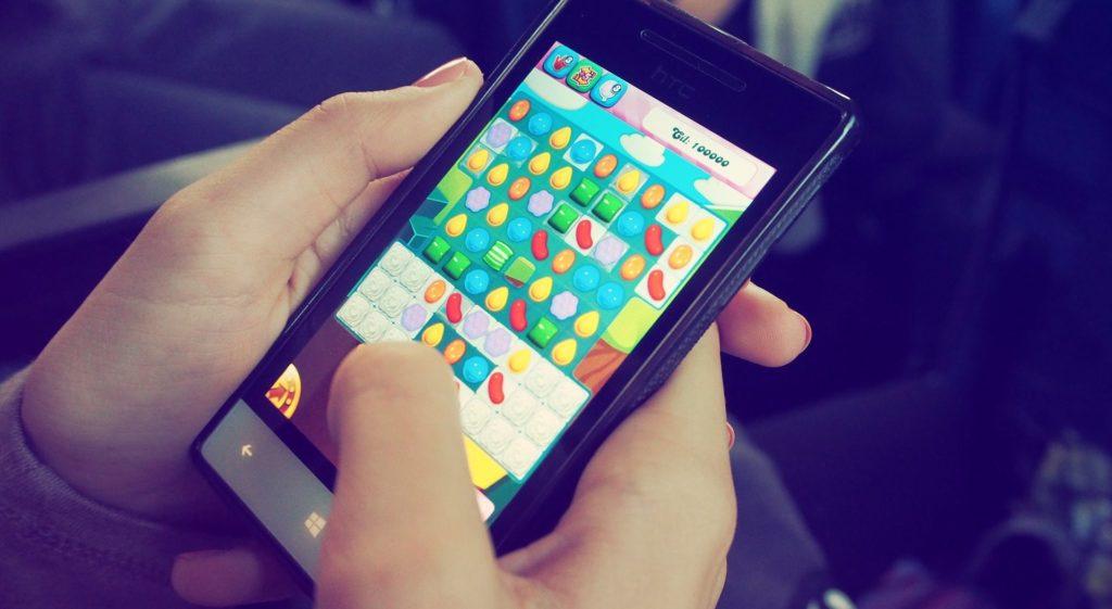 Ein Handy in einer Hand wo gerade ein Spiel darauf gespielt wird