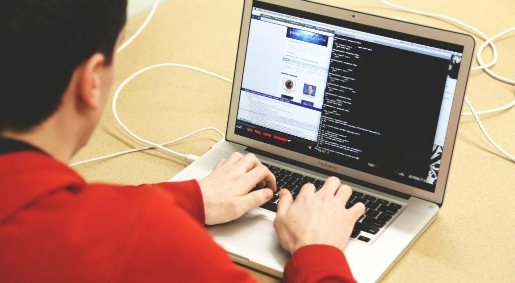 Jeune homme sur son ordinateur en train de taper des lignes de code