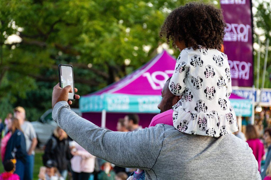 Mann mit Kind auf den Schultern die ein Selfie machen
