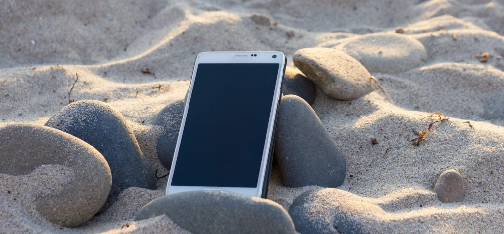 Un smartphone posé dans le sable sur une plage