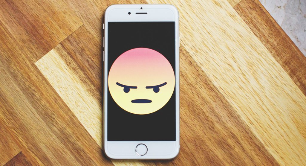 Smartphone Bildschirm mit einem großen wütendem emoji auf dem Bildschirm