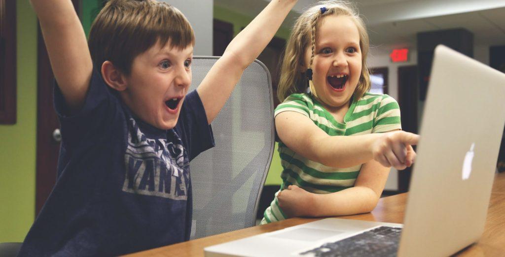 Deux enfants derrière un ordinateur, l'un est très content, l'autre montre l'écran du doigt
