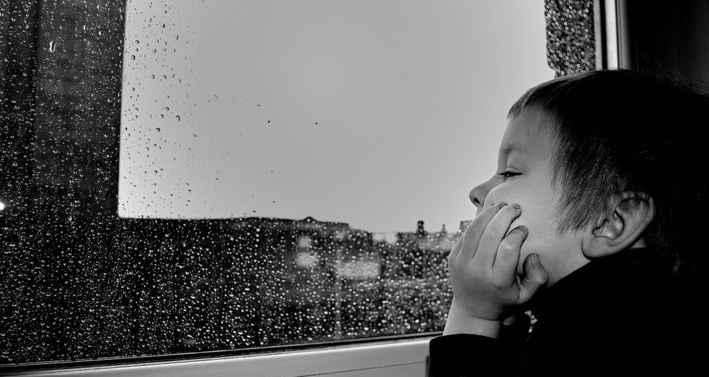 Ein Kind, das an einem regnerischen Tag aus dem Fenster schaut