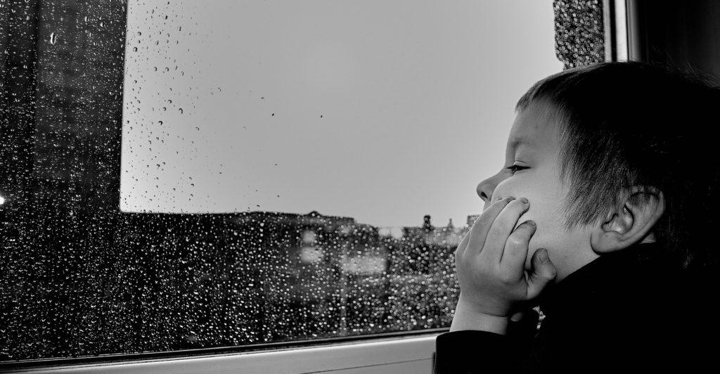Photo d'un enfant qui regarde par la fenêtre un jour de pluie