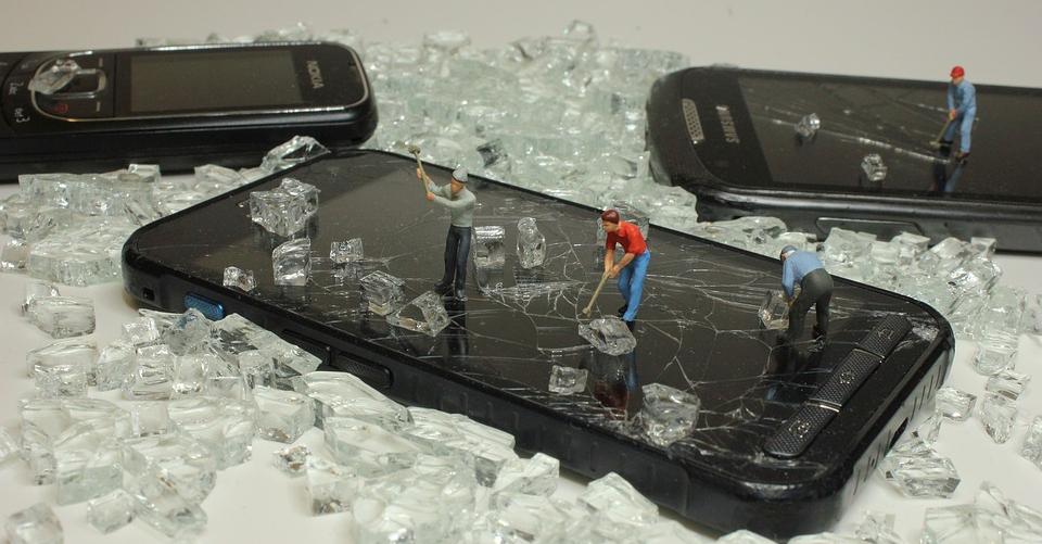 Des smartphones au milieu de verre cassé avec des mini figurines dessus