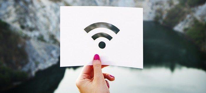 Une main tenant un papier avec le signal du wifi avec des montagnes en arrière plan
