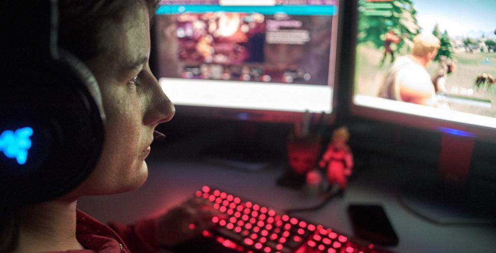 Jeune fille devant son ordinateur en train de regarder un stream de jeu vidéo