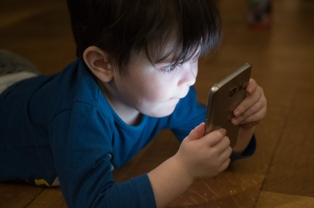 petit garçon qui regarde l'écran d'un smartphone