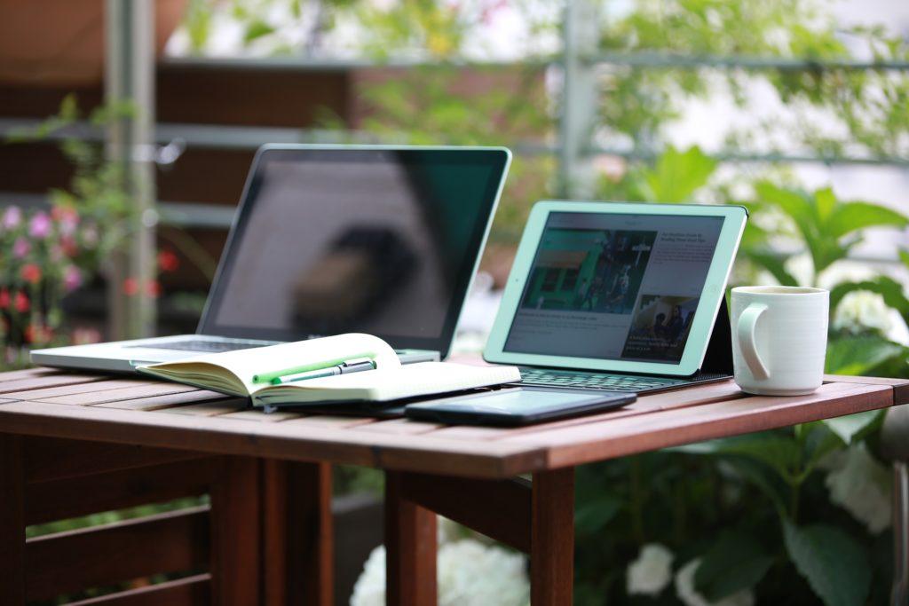 une table avec plusieurs appareils digitaux et un bloc notes