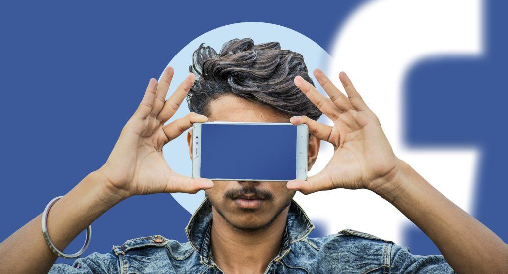 Junger Mann steht vor dem Facebook Logo und versteckt seine Augen durch sein Handy