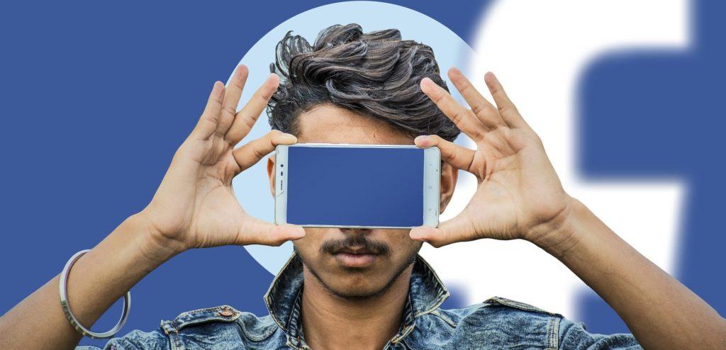 Jeune homme cache ses yeux avec son smartphone, dans l'arrière-plan il y a le logo de Facebook