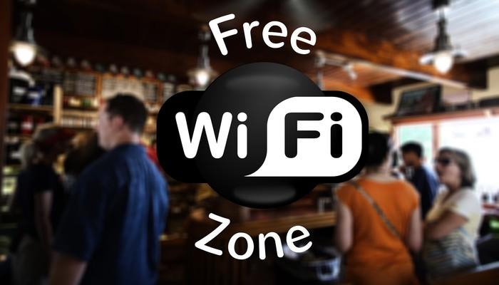 """""""Free Wifi Zone"""" et à l'arrière plan on voit un bar remplit de gens"""