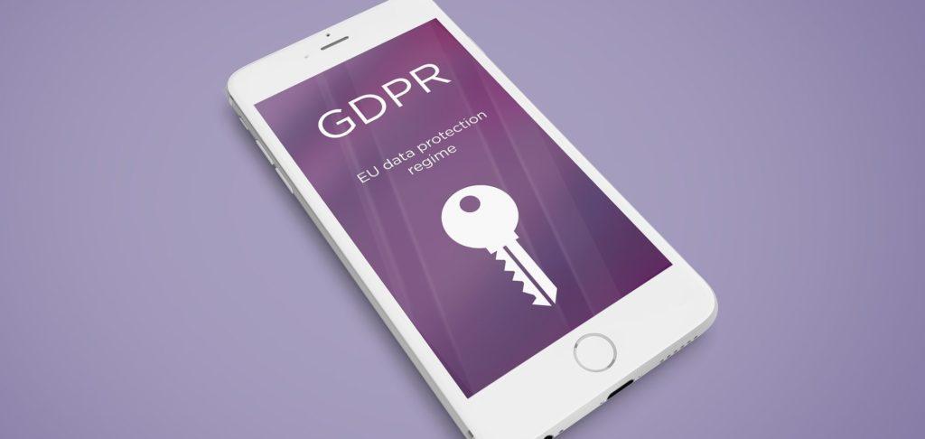 """Photo d'un smartphone avec en fond d'écran l'inscription """"GDPR, EU protection data regime"""" et une clé"""