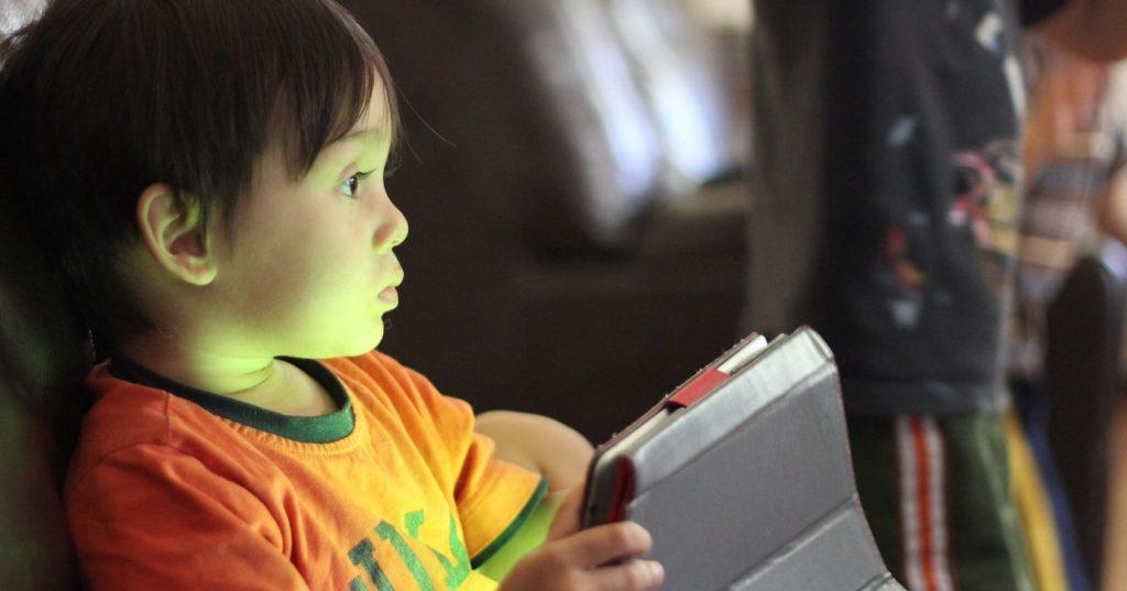 Ein kleines Kind mit einem Tablet in der Hand