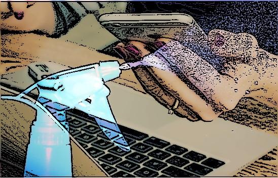 Ein Smartphone in der Hand und ein Laptop. Im vordergrund eine Sprühflasche.