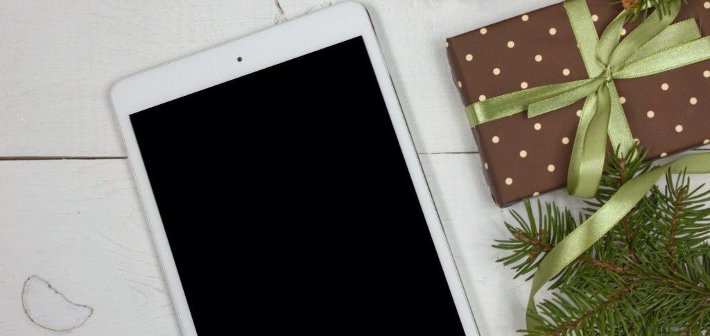 Photo d'un iPad posé sur une table à côté d'un cadeau de Noël