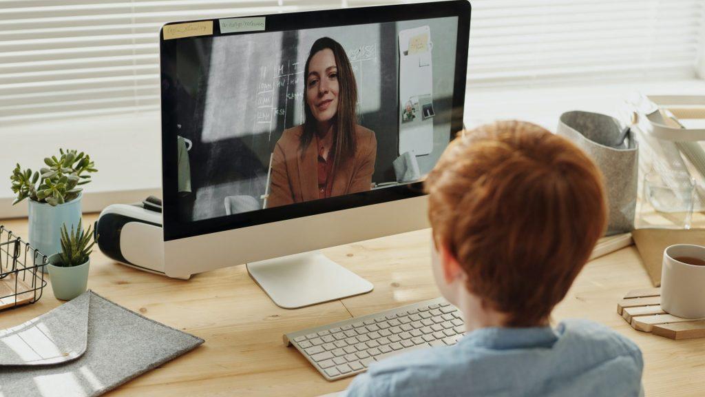 enfant assis devant un bureau en train de regarder un ordinateur avec sa professeure à l'écran
