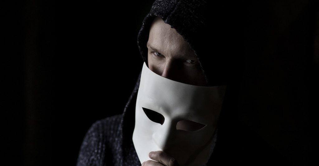 homme qui cache la moitié du visage derrière un masque