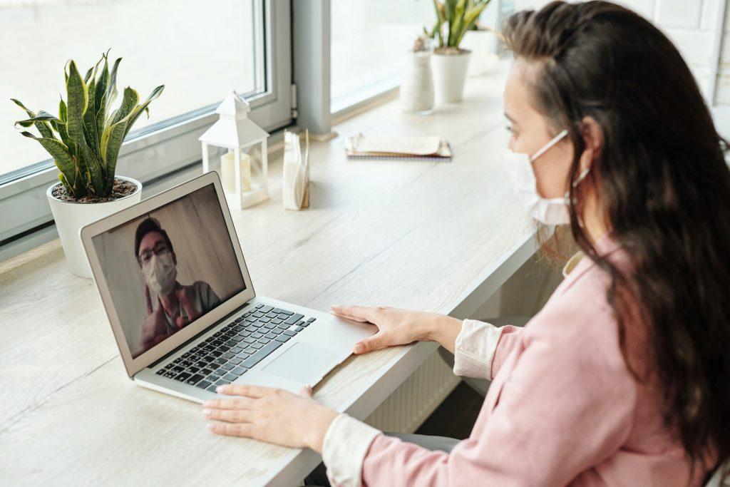 Femme en vidéoconférence avec un collègue portant tous les deux des masques sur la bouche