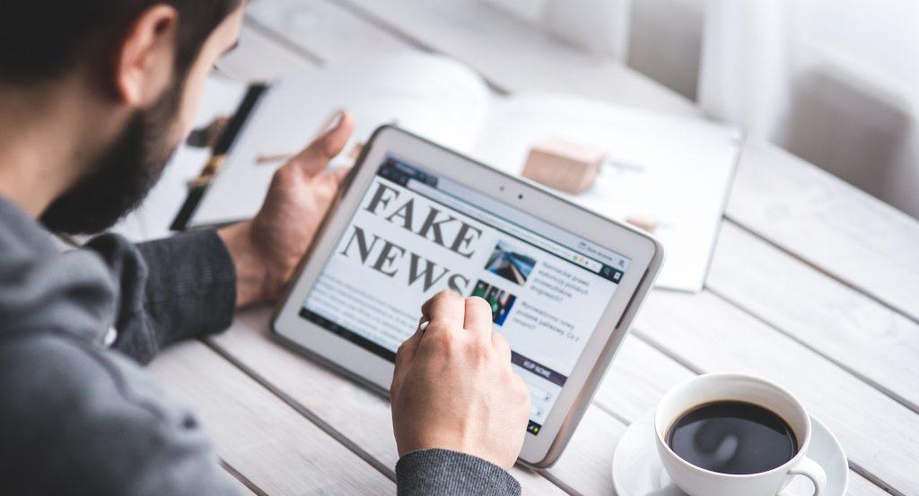 Homme regardant sa tablette avec une page d'un journal ouverte et l'inscription Fake News en grand, un café posé sur la table à côté de lui