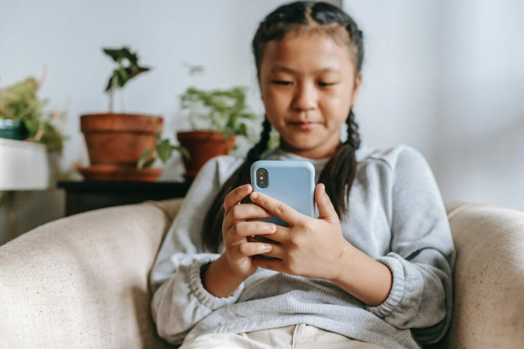 Ein junges Mädchen sitzt auf einer Couch und schaut auf ihr Smartphone.