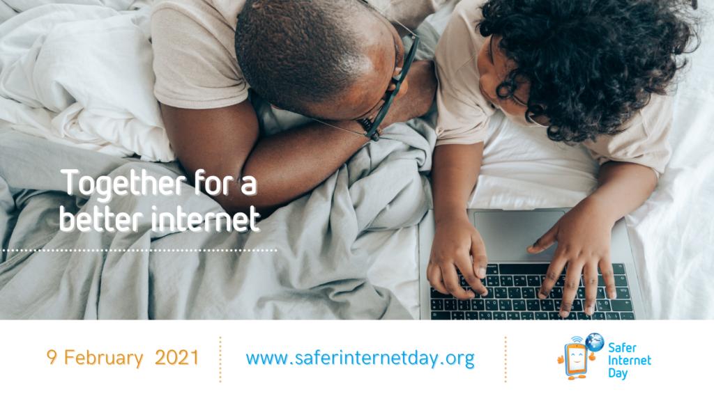 Le père et l'enfant sont allongés sur le lit et regardent ensemble l'ordinateur portable
