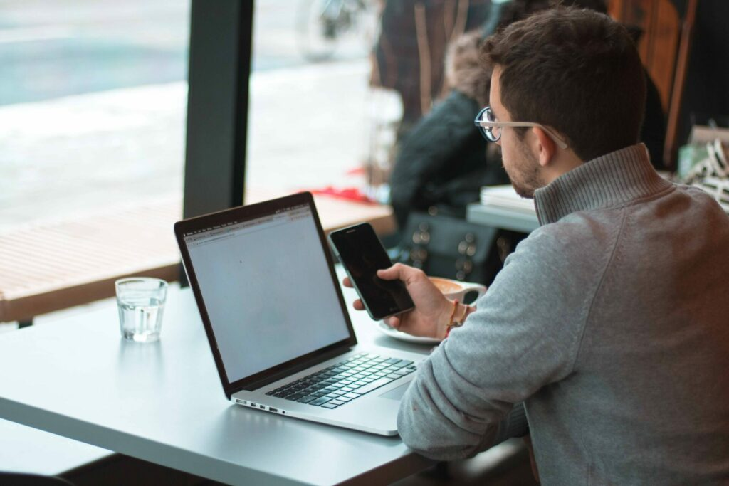 Mann mit Brille sitzt an einem Tisch mit Laptop und schaut auf sein Smartphone