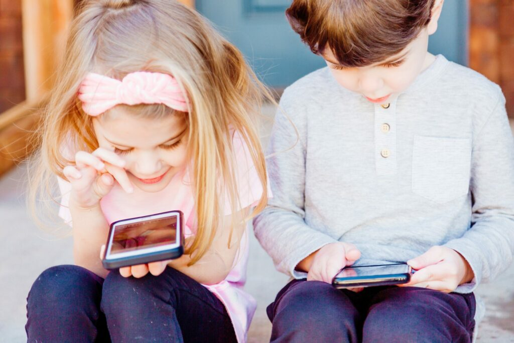 Une petite fille et un petit garçon sont assis sur un escalier et jouent avec leur smartphone.
